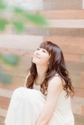 梨己未穿著白色連衣裙,她以體育坐姿勢坐著,她是日本成熟美女『服飾模特兒・平面廣告模特兒』,她的身高是171厘米,身材高挑,她的身材十分俏麗。