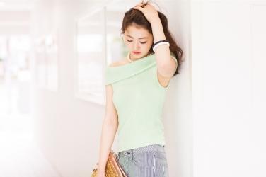 梨己未是日本成熟美女『服裝模特兒・平面廣告模特兒』,她身穿『黃綠色短袖襯衫・藍色長褲』,她的視線朝下,她的身材十分俏麗。