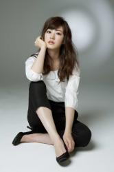 梨己未是日籍成熟美女『時裝模特兒・平面廣告模特兒』,她穿著『白襯衫・黑褲子』,她以體育坐的姿勢坐在地面上,她的身高是171厘米,身材高挑,她的身材十分俏麗。