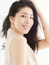 哉子曾是寶塚歌劇團的一員,目前是她在日本『成熟女性時裝模特兒・芭蕾舞教練』,這張照片是模特兒工作中使用的宣傳照片,她穿著米色女襯衫,她的身高是173厘米,身材高挑,她的身材十分俏麗
