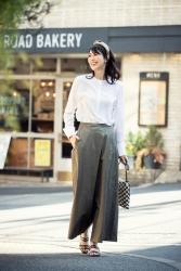 梨己未是日本成熟美女『服裝模特兒・平面廣告模特兒』,她的身高是171厘米,身材高挑,她身穿『白色長袖女襯衫・深綠色裙子』,身處時尚小鎮,她的身材十分俏麗。