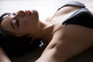 悠羽冴是日本漂亮可愛年輕『泳裝偶像・女演員』,穿著黑色比基尼泳衣,她躺著。
