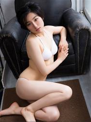 悠羽冴是日籍美麗可愛年輕『泳裝偶像・女演員』,穿著白色比基尼泳衣,她坐在地上,靠在黑色沙發上。