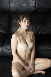 彩梨杏穿著米色比基尼泳裝,她以盘腿坐姿勢坐著,她坐在地板上,她是日籍漂亮可愛『泳裝偶像・女演員・電視藝人』。