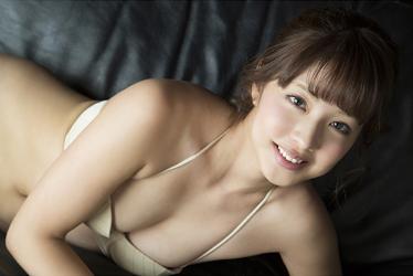 彩梨杏穿著米色比基尼泳裝,她俯臥在黑色沙發上,她是日籍漂亮可愛『寫真女優・女演員・電視藝人』。